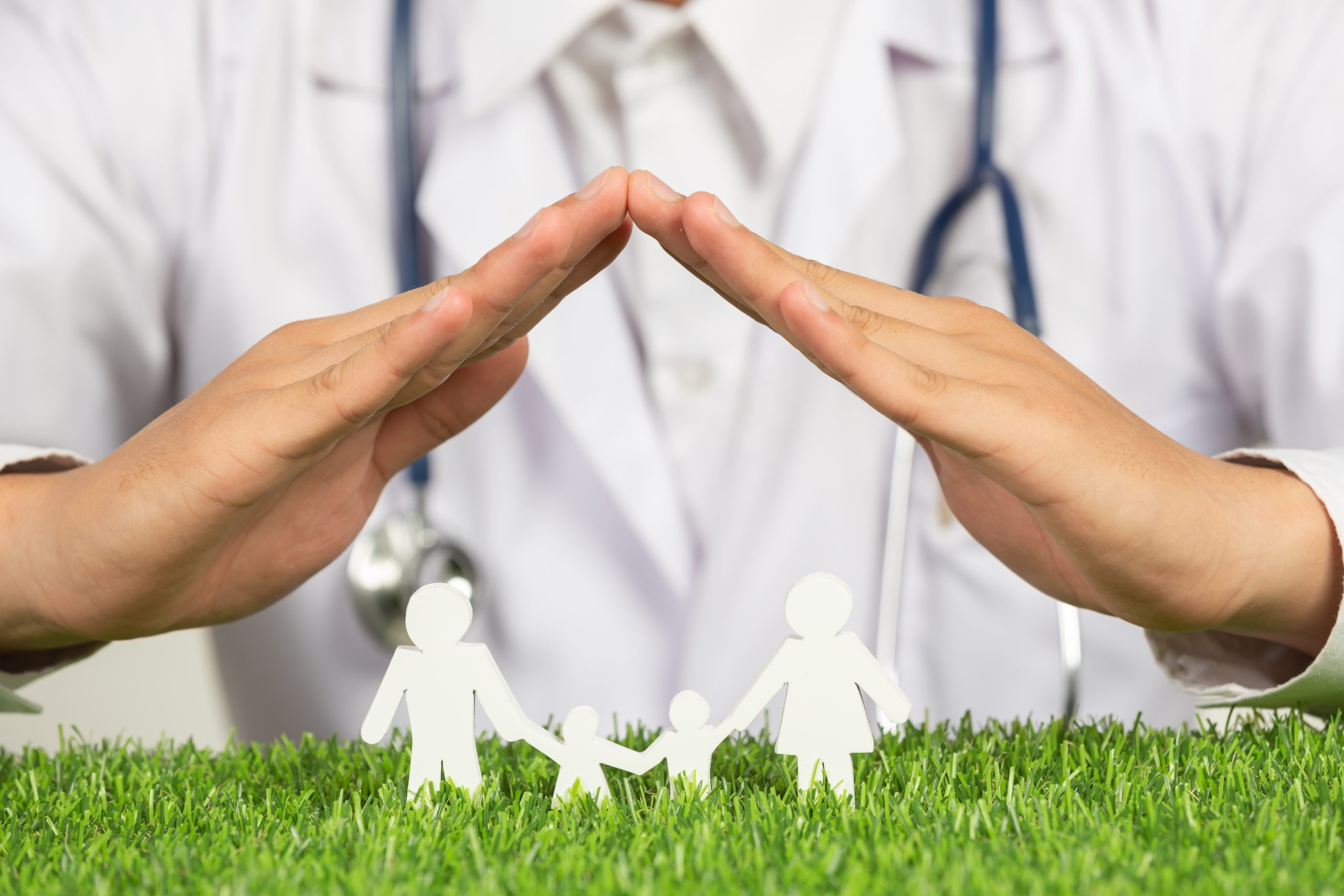 close up picture of doctor's hands posting symbol of home above